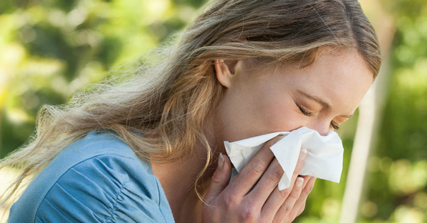 woman sneezing due to spring allergies in wisconsin