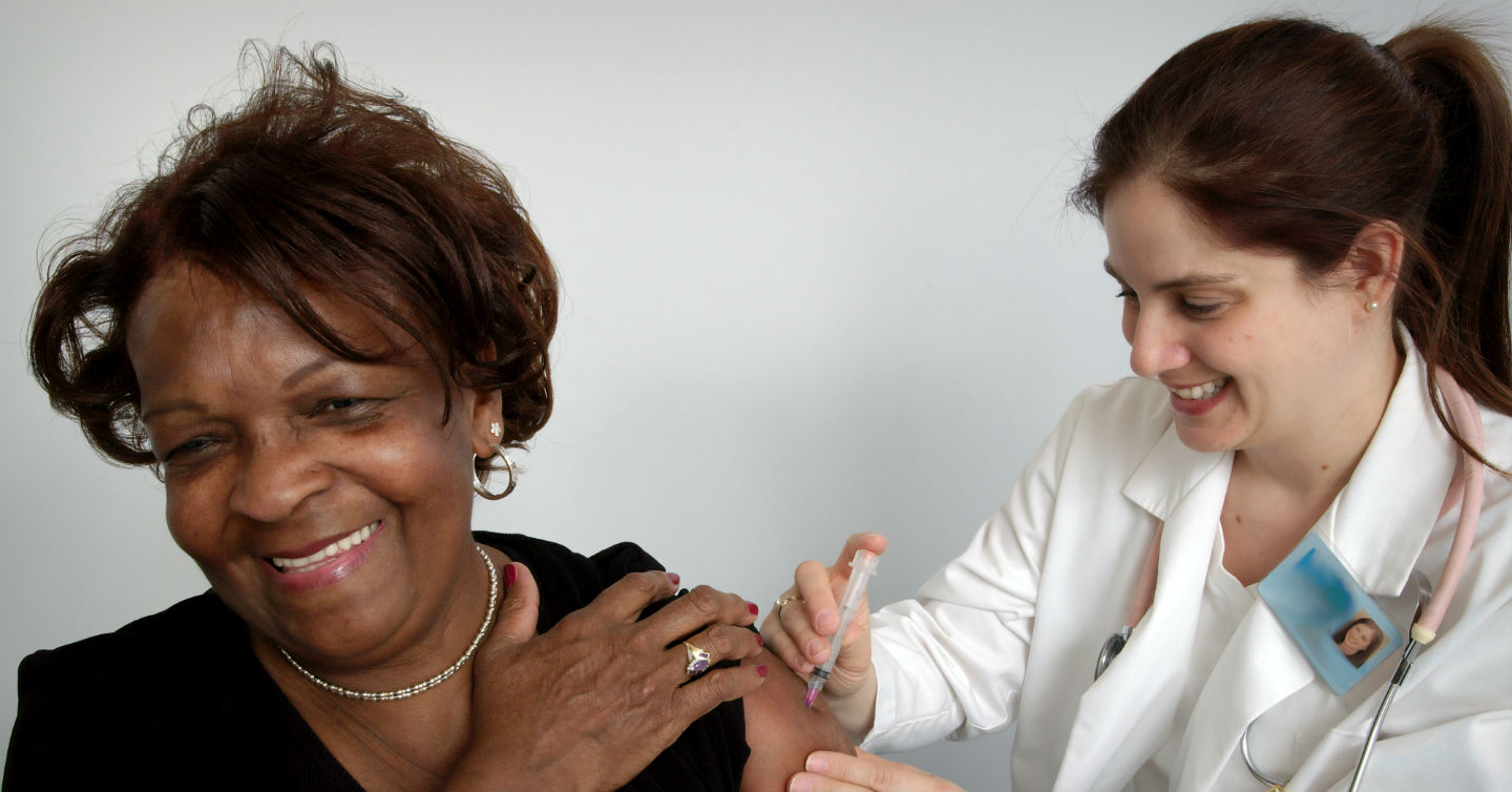 woman administering vaccine to another woman