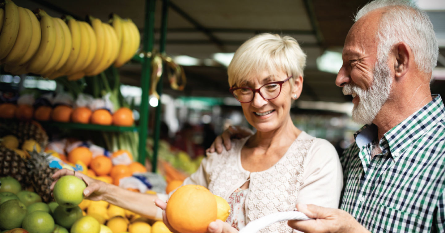 Medicare-aged couple shopping for fruit at an outdoor market
