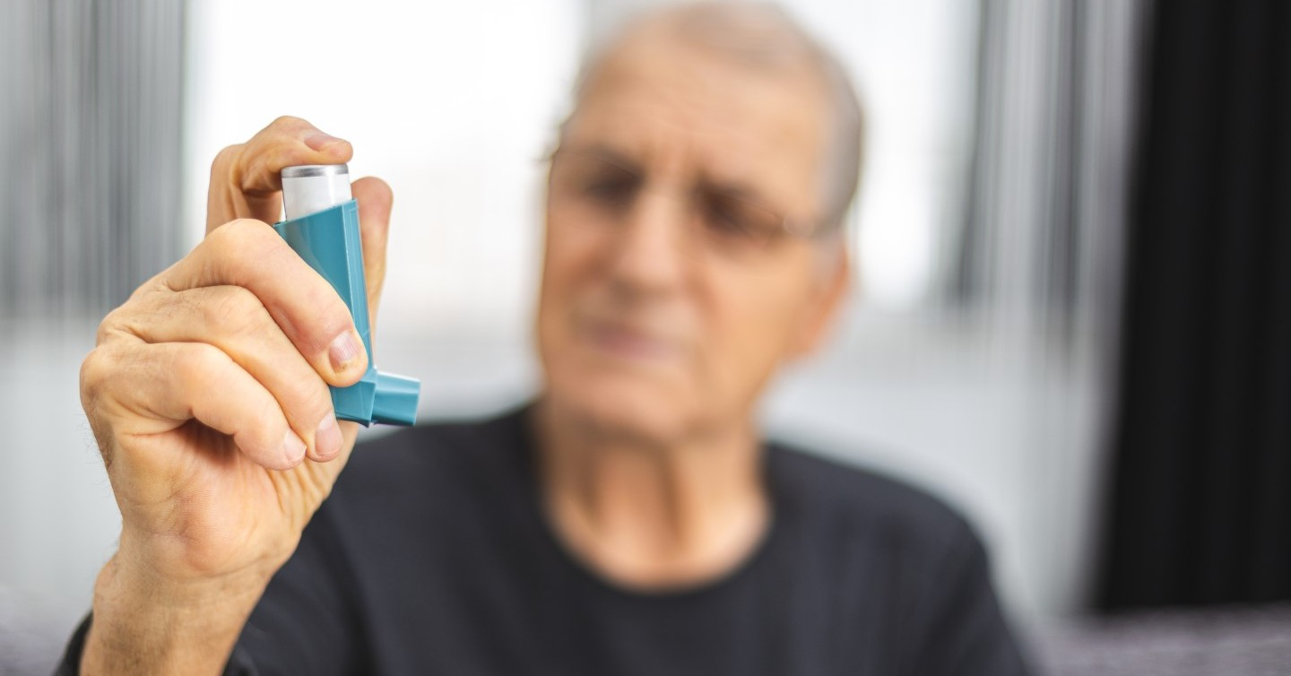 person with asthma holding asthma inhaler for attack